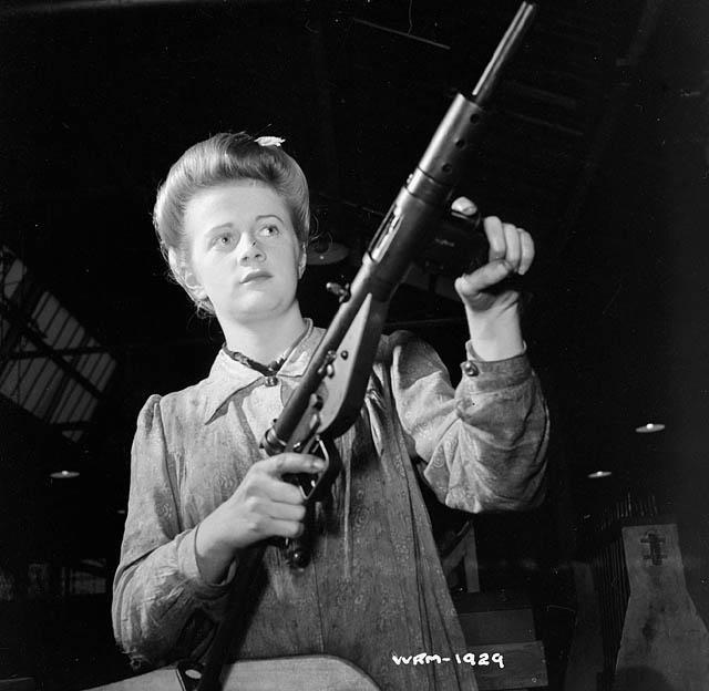 A worker holding a finished Sten Gun in a factory