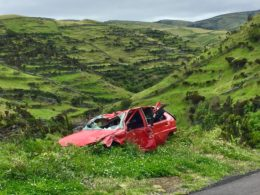 photo of broken red car on grass