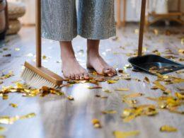 woman in gray dress standing on brown wooden floor