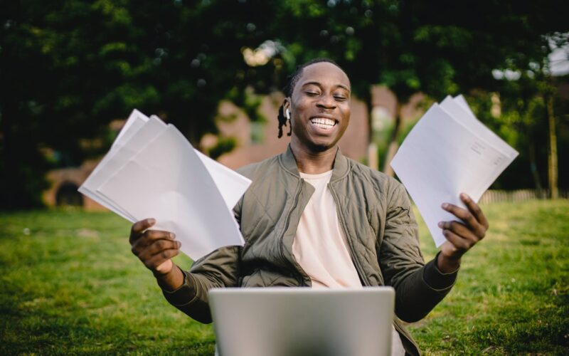 student with documents and laptop happy about getting into university