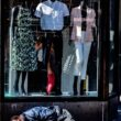 photo of homeless man sleeping in front of clothing store