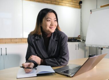 cheerful asian executive at table with laptop and diary