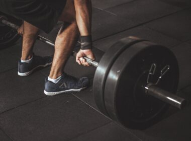 man in black reebok shoes about to carry barbell