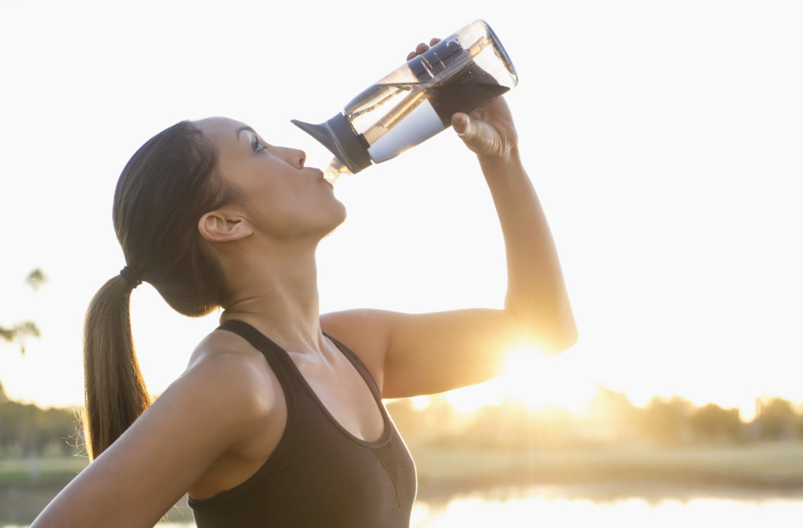 Mixed race runner drinking water outdoors