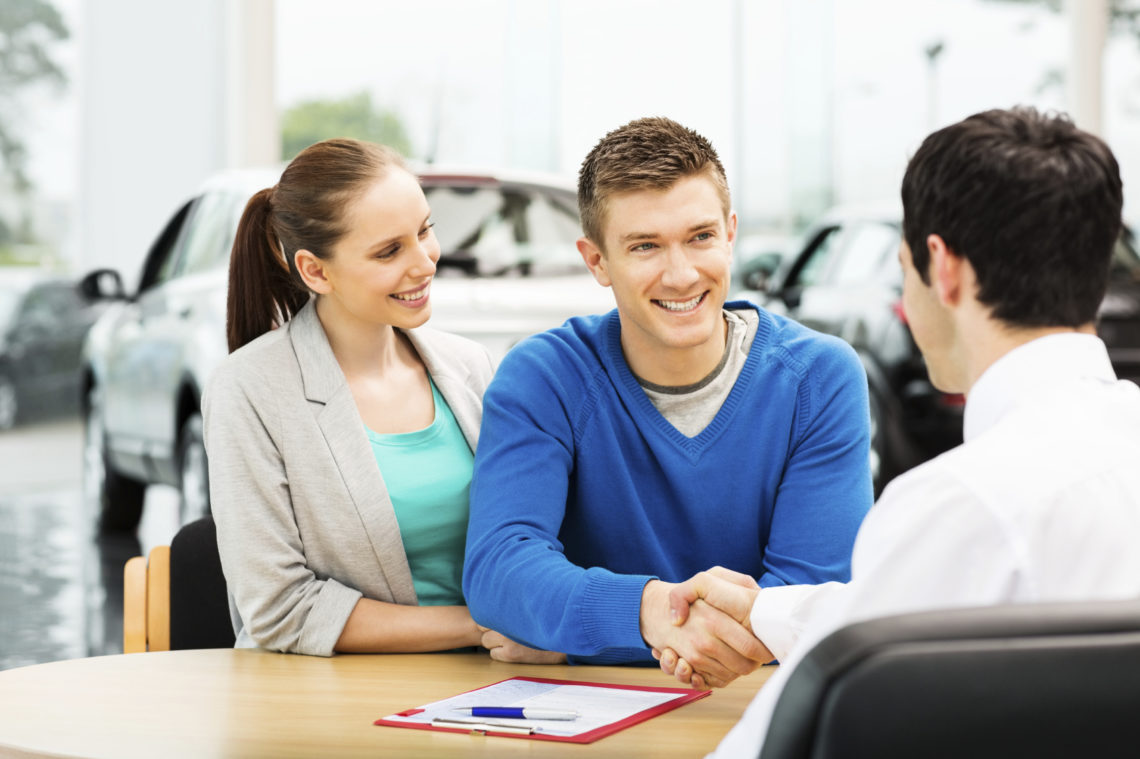Happy young man shaking hands with salesperson at car showroom. Horizontal shot.