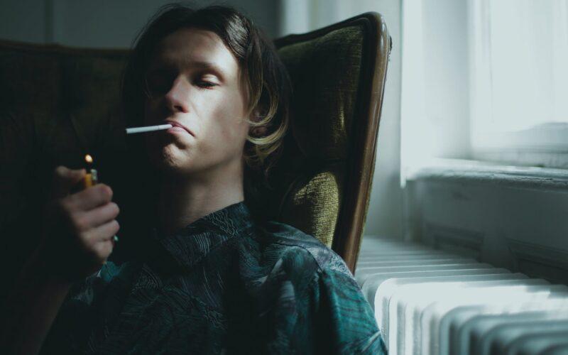young man smoking at home