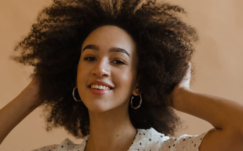 cheerful young black lady touching afro hair and smiling in studio