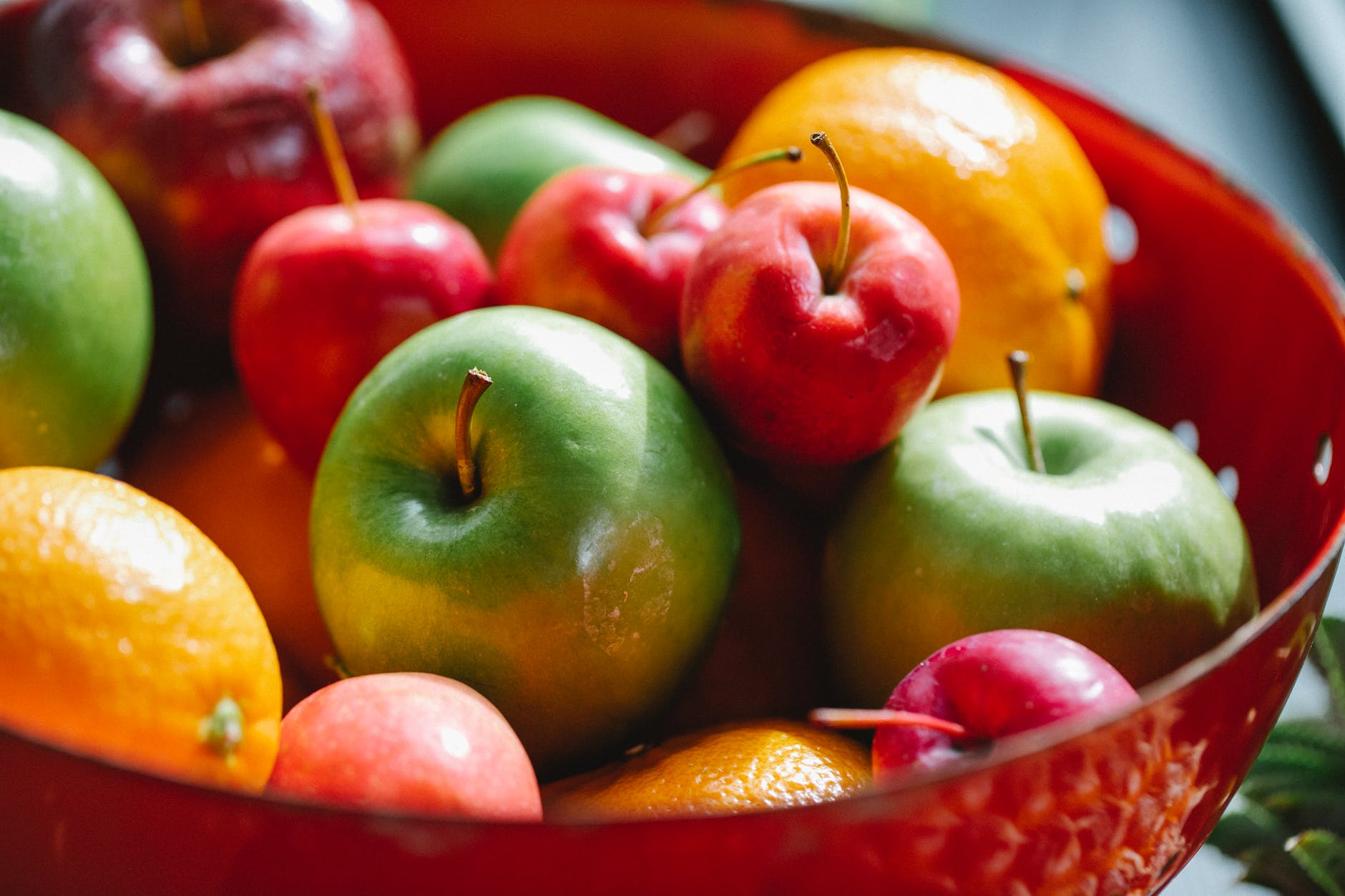 delicious multicolored apples and oranges with mandarins located in red bowl