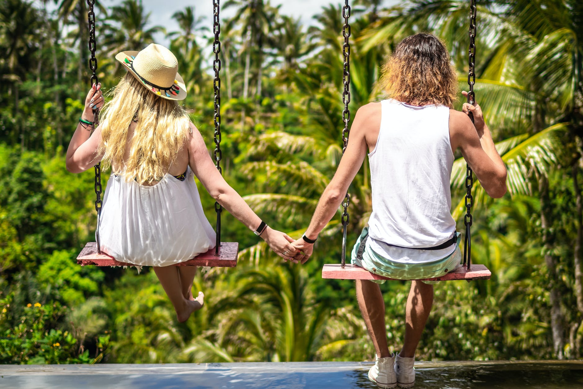 back view photo of couple on swings holding hands