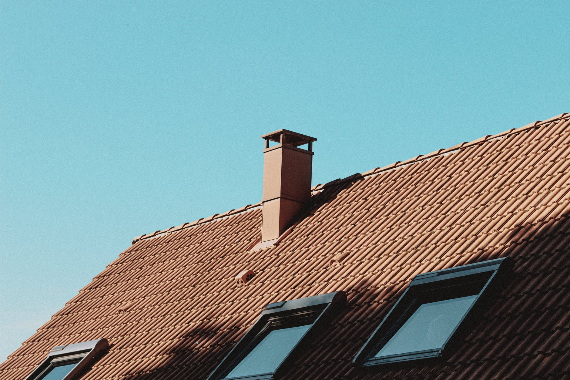 detail of house roof with chimney and attic windows